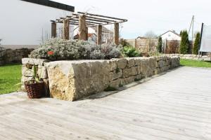 Eine bepflanzte Steinmauer harmoniert mit Holzterrasse
