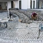 Ein Steinsetzer setzt die Steine einzeln